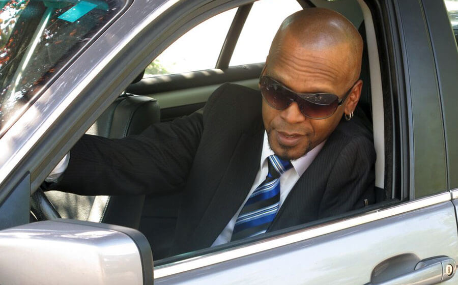 Man with Scalp Micropigmentation in a suit driving a car