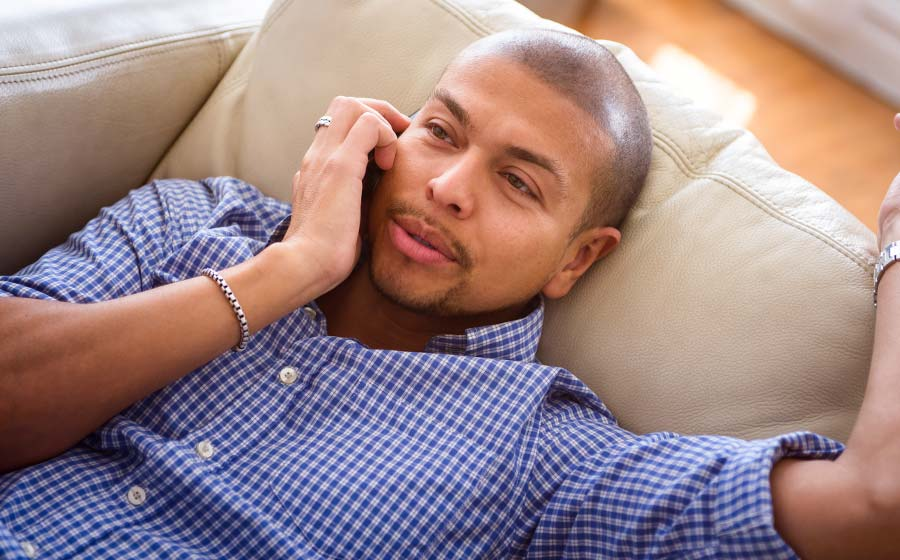 Man with SMP relaxing on the couch talking on the phone